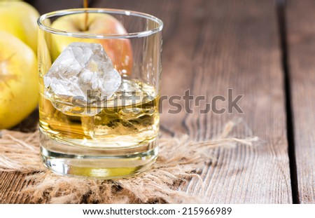 Apple Liqueur in a glass (close-up shot) on wooden background - stock photo