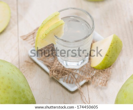 Apple Liqueur in small glasses with fruits - stock photo