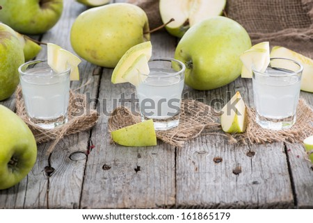 Apple Liqueur Shots on wooden background - stock photo