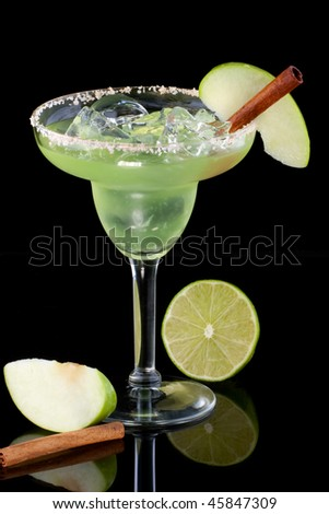 Apple Margarita in chilled glass over black background on reflection surface, garnished slice of green apple and cinnamon stick. Most popular cocktails series. - stock photo