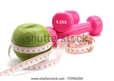 Apple, measuring type and dunbbell - stock photo