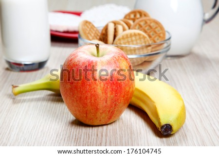 Apple, milk, banana and cookies on table