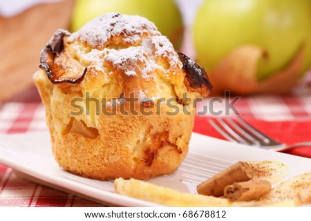 Apple muffin on a white plate with apples and leaves in the background. Studio shot. Selective focus, extra shallow DOF.