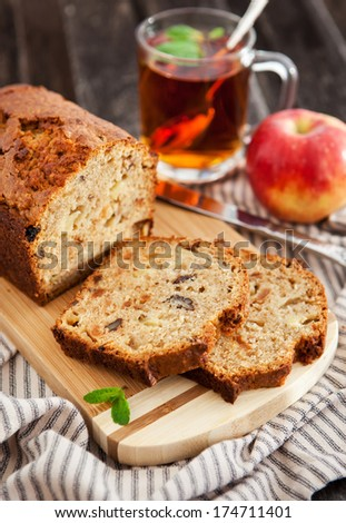 Apple nut cake on wooden board with cup of tea on the background  - stock photo