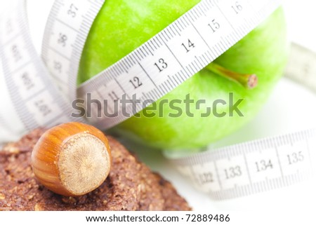 apple, nuts, cookies and measure  tape isolated on white