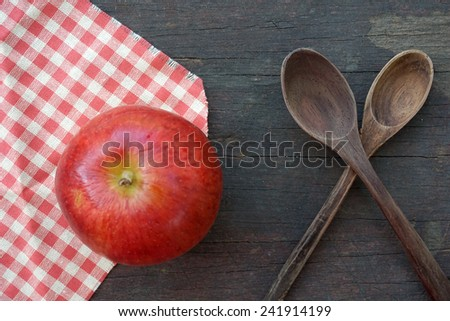 apple on checked tablecloth on wooden table - stock photo