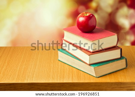 Apple on old vintage books over bokeh background. Back to school concept - stock photo