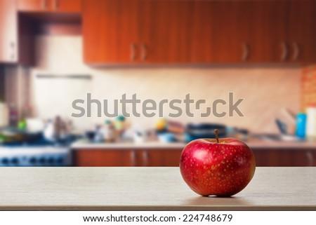Apple on the kitchen table - stock photo