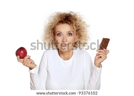 Apple or chocolate / Beautiful blond woman doubting between healthy or unhealthy food