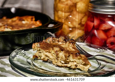 Apple pancake breakfast baked in cast iron skillet with mason jars of fruit