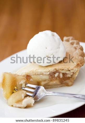 Apple pie alamode on a wooden table - stock photo