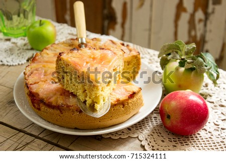 Apple pie and apples on a wooden table. Rustic style, selective focus.