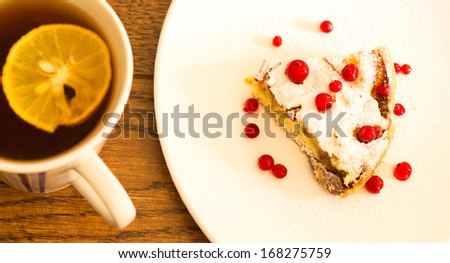 Apple pie, cup of black tea with lemon on the wooden table