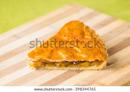 Apple pie cut into portions. Close-up on a wooden board .