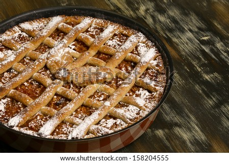 Apple pie in baking tray on rustic table - stock photo