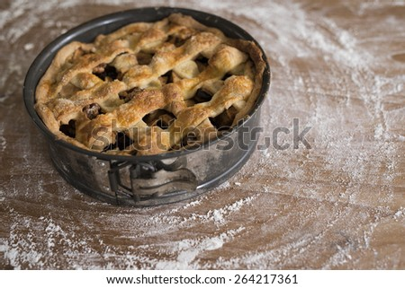 Apple pie in spring cake bin, on a wooden table covered with flour, shallow DOF - stock photo
