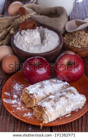 apple pie on a wooden table with flour and grain in the background