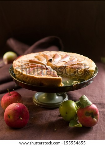 Apple pie on cake stand in vintage style, low key, selective focus - stock photo