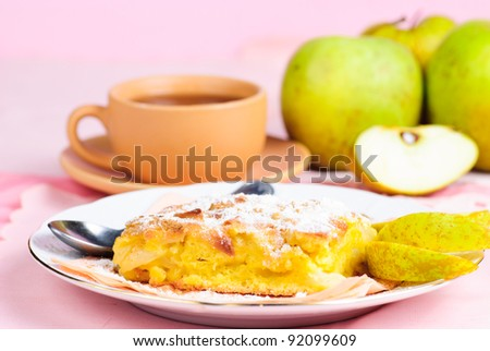 Apple pie on plate with spoon and cup, fruits and pink placemat on background
