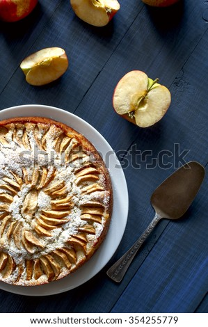 Apple pie on white plate, apples and pieces of apple on deep blue background, vertical view - stock photo