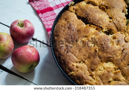Apple pie on wooden background in a pan