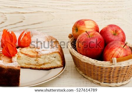 Apple pie, Physalis flowers and ripe apples on a light wooden table, close-up