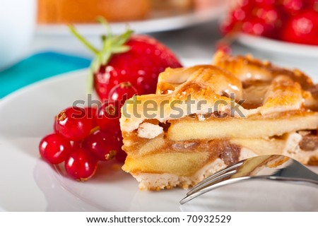 Apple pie served with red currants and strawberry.