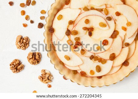 Apple pie with raisins and nuts preparation, Raw homemade baking on white rustic kitchen table - stock photo