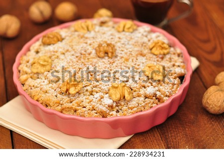 Apple pie with walnuts and powdered sugar in a ceramic lilac form, a cup of coffee on a brown wooden background - stock photo