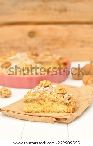 Apple pie with walnuts and powdered sugar in a ceramic lilac form on a white wooden background - stock photo