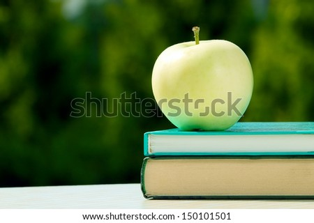 Apple placed on books with green nature background - stock photo