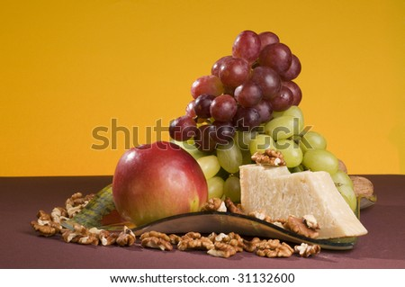Apple, red and green grape, cheese lying on a glass color plate.