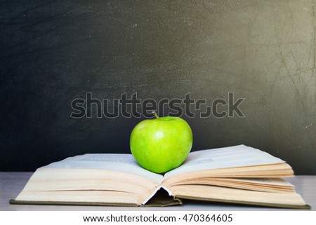 Apple resting on the book with chalk board as background.Back to school.