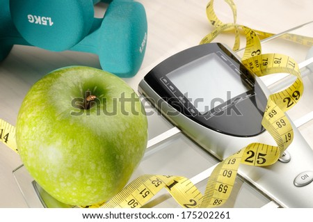 apple, scale and dumbbells for a healthy life