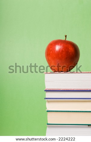 apple sitting on top of a pile of books