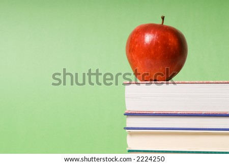 apple sitting on top of books in a classroom
