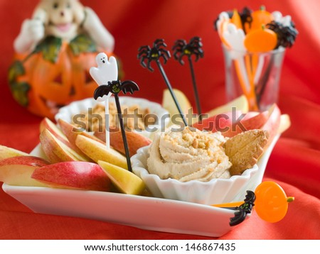Apple slices with butter cream and cookie for halloween party, selective focus - stock photo