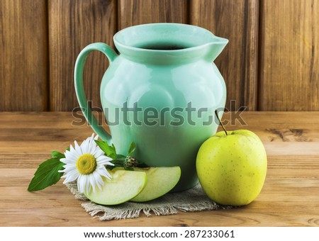 Apple slices with camomile flower and green pot on wooden background