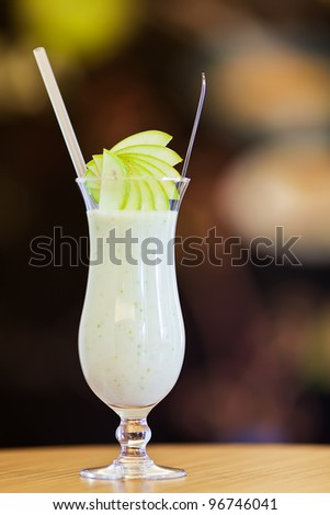 Apple smoothie in a hurricane glass with straw and fresh apple slices on dark background and wooden table