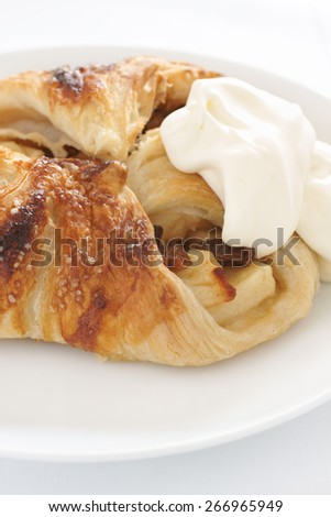 Apple strudel Danish pastry filled with apple cinnamon and sultanas served with whipped cream - stock photo