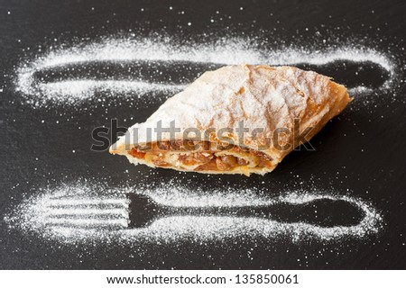 Apple strudel on a slate board with the design of icing sugar - stock photo