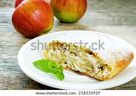 Apple strudel with cream cheese on a dark wood background. tinting. selective focus on the strudel - stock photo