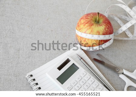 Apple, tape measure, notebook and calculator background for diet plan, weightloss plan - stock photo
