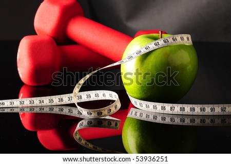 apple, tapeline and dumbbells - stock photo