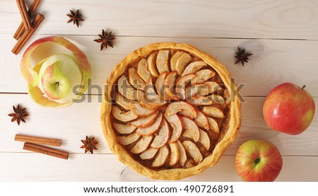 Apple tart with cinnamon and apples on a white wooden background - top view