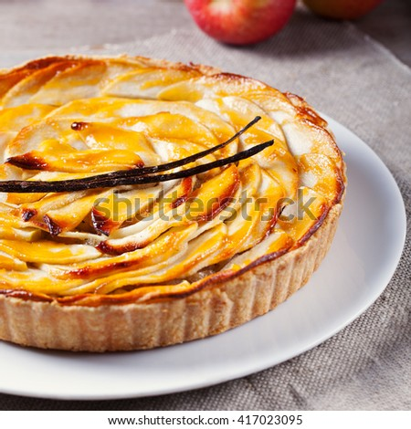 Apple tart with vanilla pod on a white plate Traditional holiday dessert Wooden rustic background - stock photo