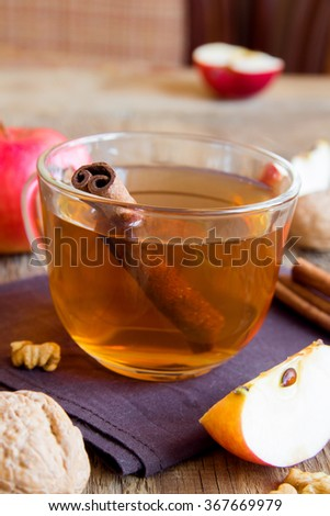 Apple tea with cinnamon over rustic wooden background - stock photo