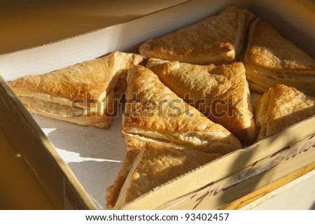 Apple turnovers fresh out of the box ready for breakfast - stock photo