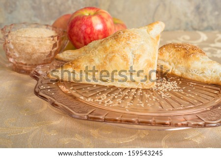 Apple turnovers on an antique glass plate next to a bowl of raw sugar and some apples - stock photo
