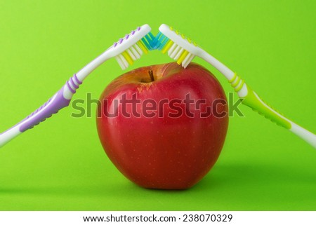 apple with a toothbrush, isolated on a green background. healthy dental care concepts - stock photo